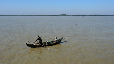 A fisher in a boat in the Ayeyarwady Delta, Myanmar